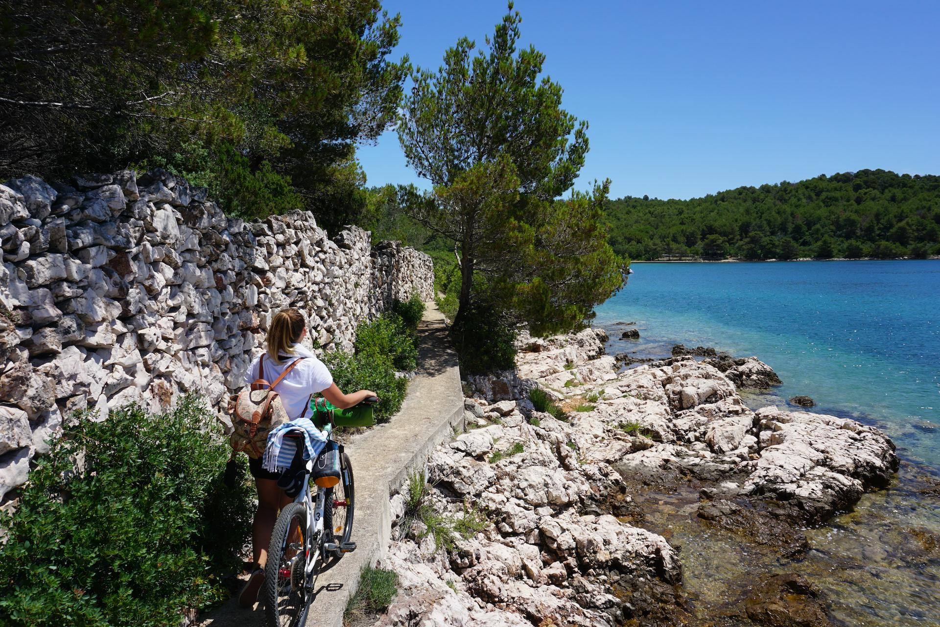 A girl with a bike by the beach Sabuša; ugljan self guided bike tour