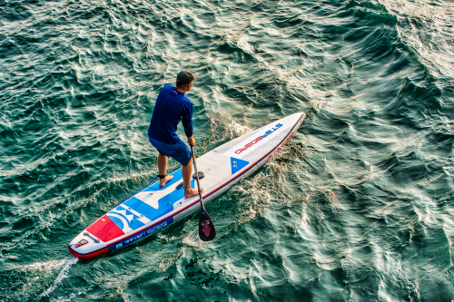 a man on a stand up paddling board - sup board rental
