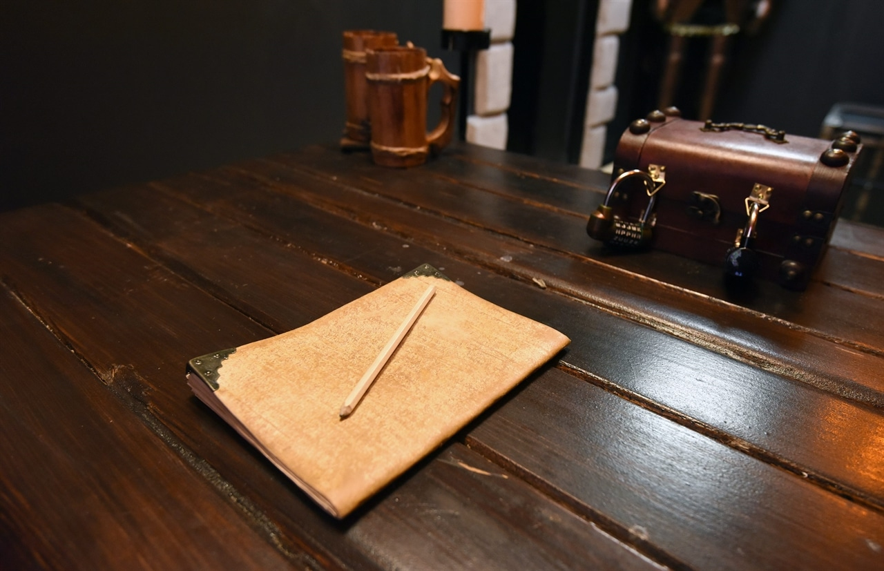 a notebook and a pencil on a wooden desk