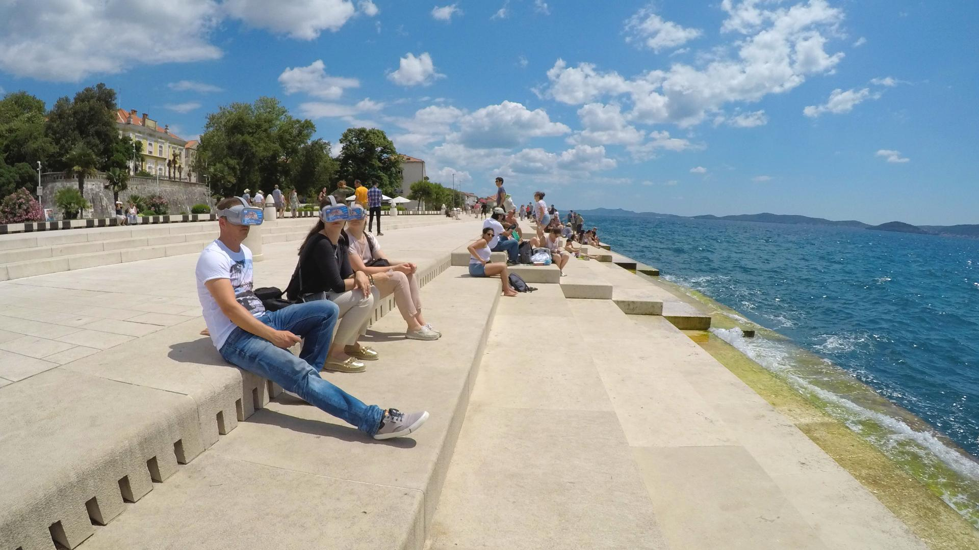 People sitting on the steps by the sea during Zadar Virtual Tour