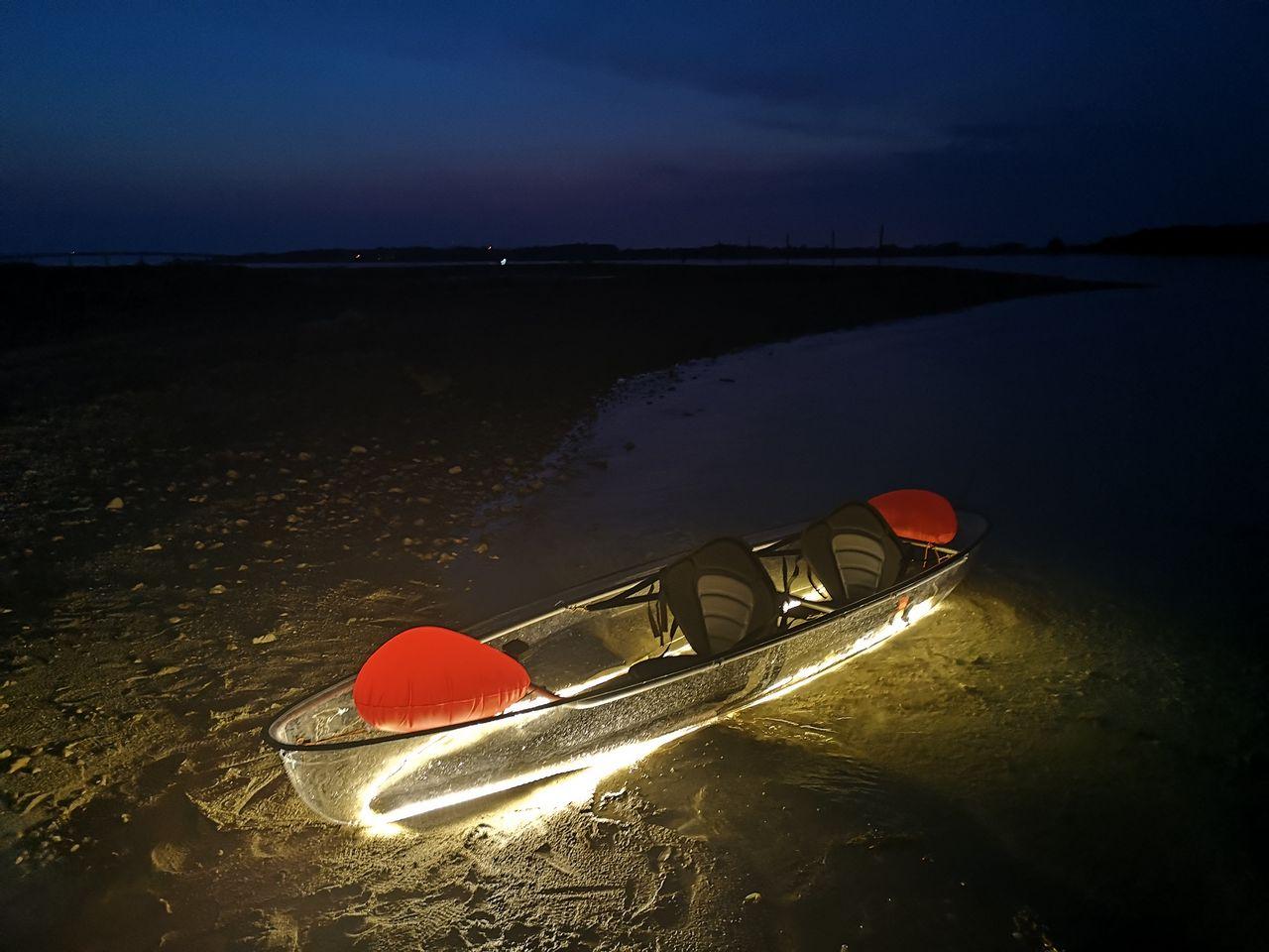 transparent kayak on the sea by nighr