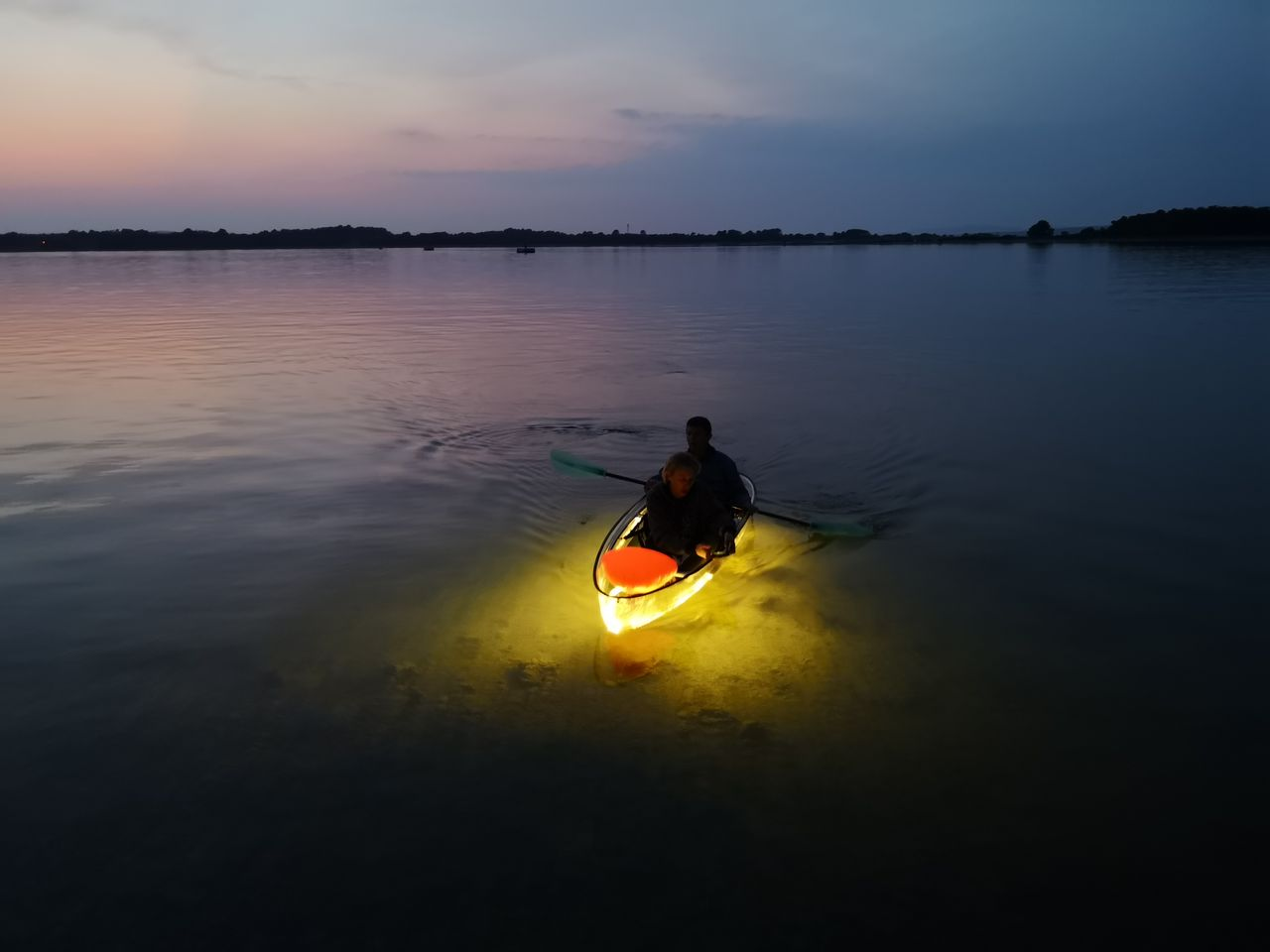 a man paddling in a kayak with lights by night