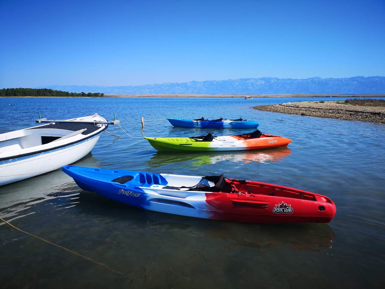 a blue-white-red and a green-white-orange kayak in the sea