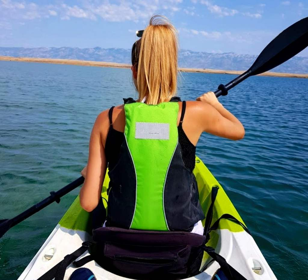 a back of a blond long haired woman paddling in a kayak