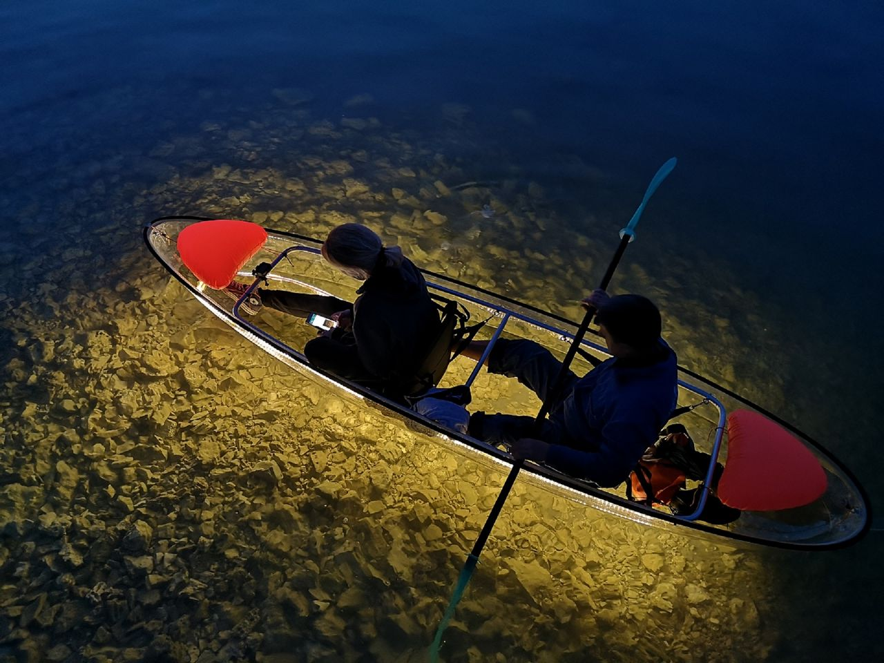 aerial view on two people in a kayak paddling by night