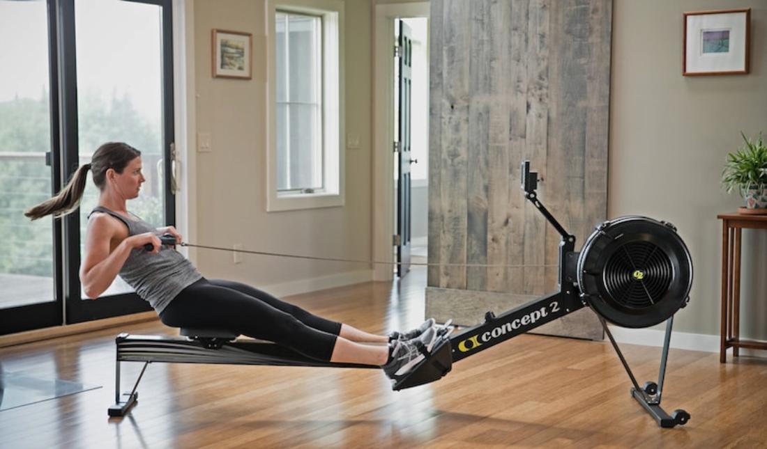 woman using indoor rowing machine