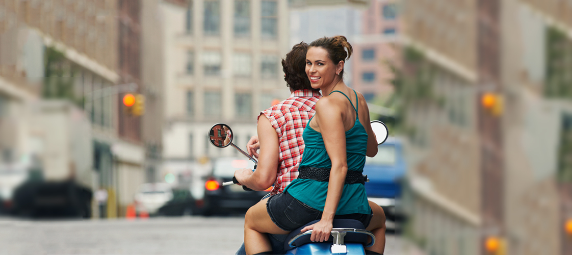 a man and a woman riding a scooter